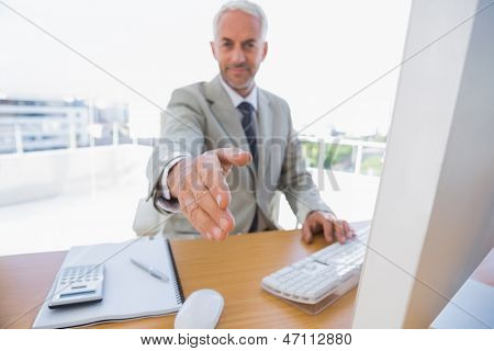 Happy businessman reaching arm out for handshake in his office