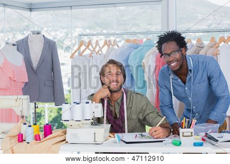 Fashion designers working together in a creative office and smiling to the camera