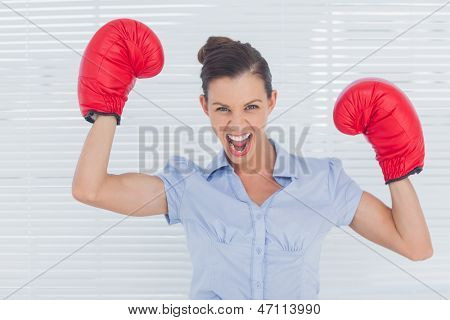 Businesswoman in boxing gloves cheering in the office