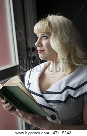 Beautiful Young Woman With Blond Hair Reading Book