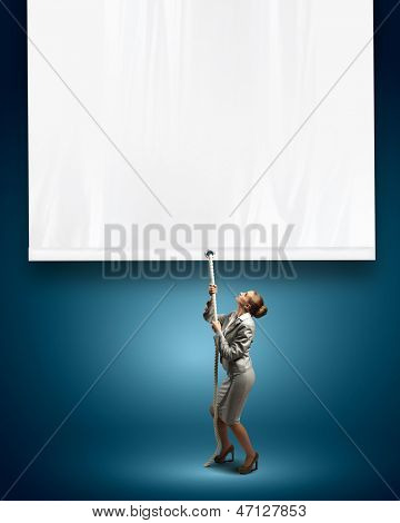 Image of young businesswoman pulling blank banner. Place for text