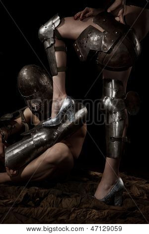 A knight in armour worshiping and holding female leg