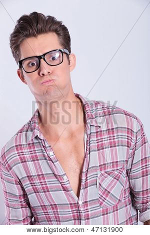 closeup portrait of a casual young man goofing around blowing his cheeks while looking at the camera. on gray background