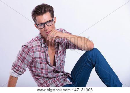 Ausschnitt-Bild eines jungen Mannes lässig posiert auf dem Boden mit der Hand am Kinn und Blick auf th