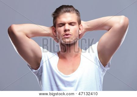 young fashion man holding his hands at the back of his head and his eyes closed. on gray background