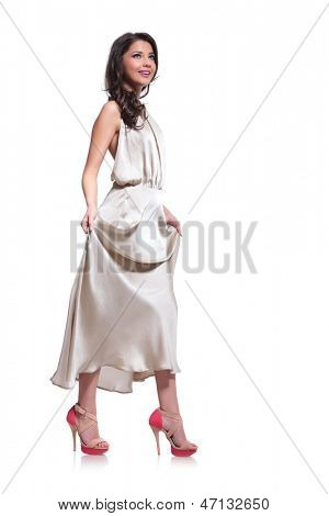 full length photo of a young beauty woman holding up her dress with both hands while looking upwards, away from the camera. isolated on white background