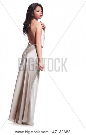 full length photo of a young beauty woman touching her shoulder while looking down, away from the camera. isolated on white background