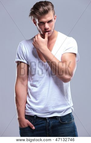 young fashion man holding his hand in his pocket and his thumb on his lower lip while looking at the camera. on gray background