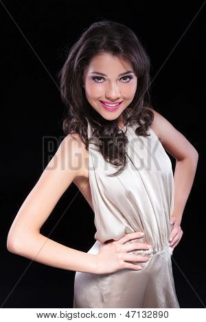 young beauty woman holding both her hands on her hips and smiling for the camera. on black background