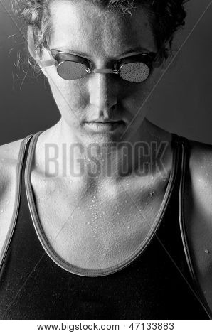 portrait of a looking downwards concentrated woman swimmer, blue toned on blue background