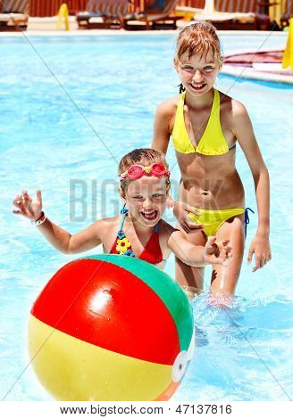 Little girl  playing ball in swimming pool.