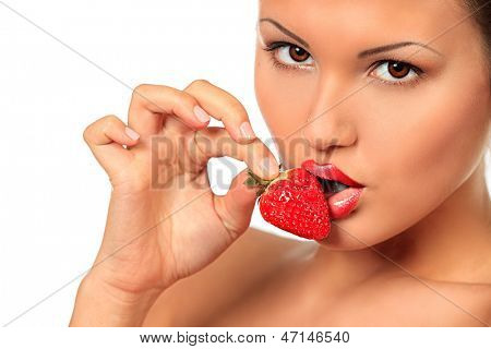 Seductive young woman eating a strawberry. Isolated over white.