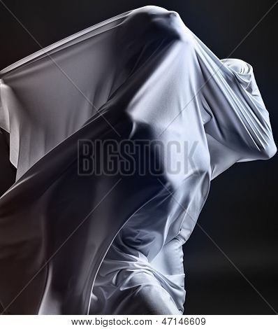 Art photo of a female silhouette breaking through the fabric. Struggle concept.