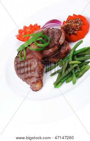 grilled meat beef steaks strips on white plate with sweet pea and tomatoes isolated over white background
