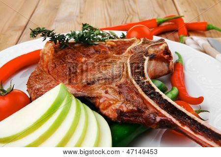 savory : grilled spare rib on white dish with thyme pepper and tomato on wooden table