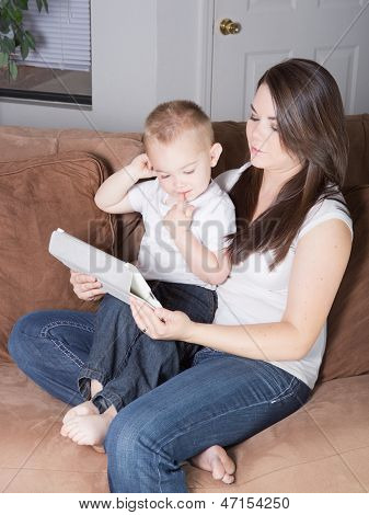 Young mother showing toddler to read on tablet