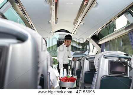 ROAD FROM BURSA TO ISTANBUL, TURKEY - AUGUST 20: Steward serves drinks to passengers during the travel from Bursa to Istanbul, Turkey on August 20, 2011. Turkish bus companies have luxury buses