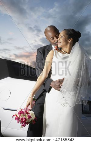 Newlyweds hugging by limo