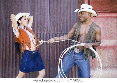 Jovem em roupa de cowboy laçar a namorada dele