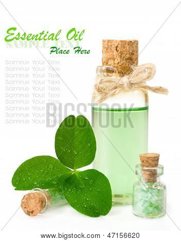 Bottle Of Scented Oil And Leaf Clover In Drops Of Water