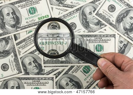 Hand With Magnifying Glass On A Background Of Money