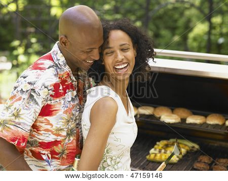 Couple laughing and having barbecue together