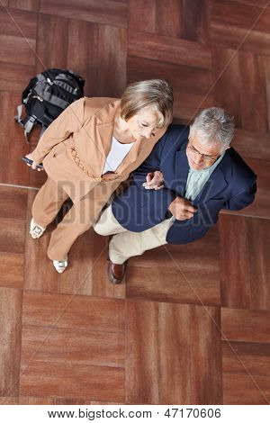 Two senior people walking together with a suitcase