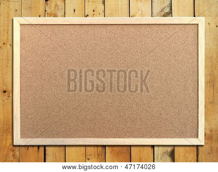 Cork Board With Wooden Frame On Wooden Background