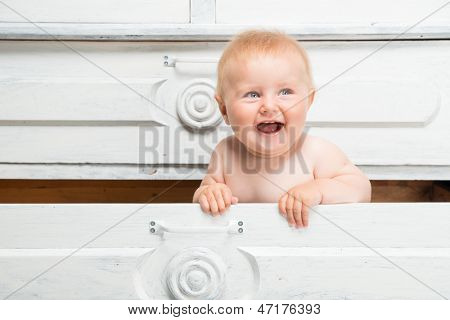 Cute smiling little baby in a drawer