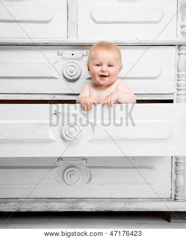 Smiling little baby in a drawer