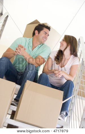 Couple Sitting On Staircase With Boxes In New Home Smiling