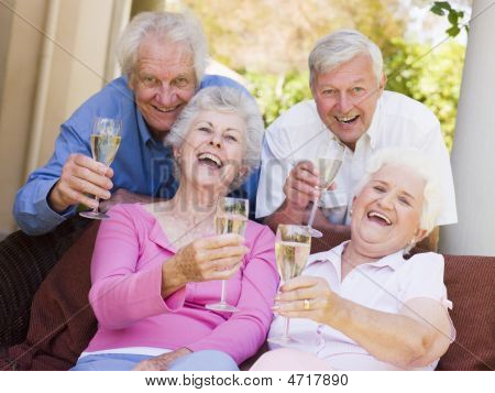 Two Couples On Patio Drinking Champagne And Smiling