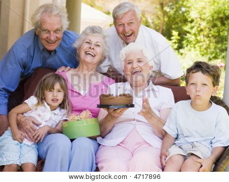 Grandparents And Grandchildren On Patio With Cake And Gift Smiling