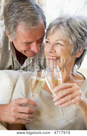 Couple In Living Room Toasting Champagne And Smiling