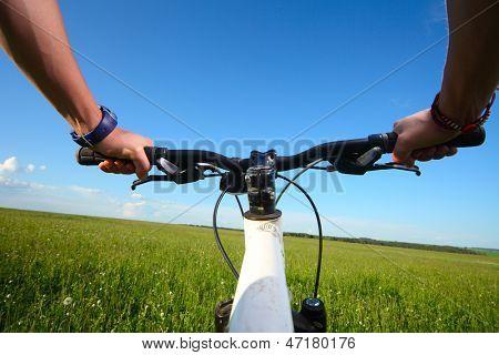 Hände halten Lenker eines Fahrrades auf einer grünen Wiese in sonniger Tag
