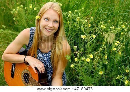Mujer sentada afuera con guitarra