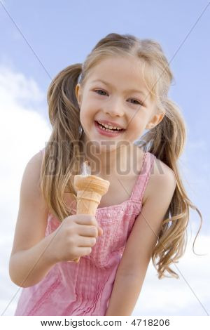 Young Girl Outdoors Eating Ice Cream Cone And Smiling
