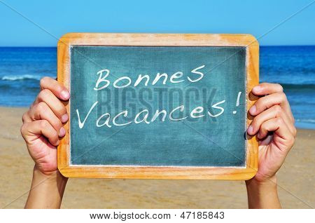someone holding a blackboard on the beach with the sentence bonnes vacances, happy vacations in french, written on it