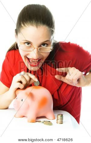 Excited Woman Putting A Coin Into Her Piggy Bank