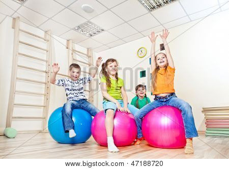 Cheerful kids on large gym balls with their hands up