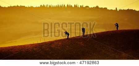 Val d'Orcia after sunrise with photographer, Tuscany, Italy