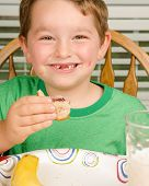 stock photo of finger-licking  - Child eating messy peanut butter and jelly sandwich with milk and fruit for healthy lunch - JPG