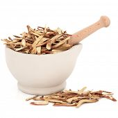 Chinese herbal medicine of licorice root in a stone mortar with pestle over white background.