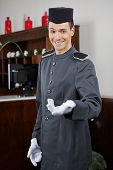 Happy concierge greeting guests in hotel on welcome