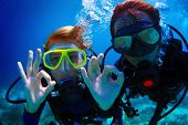 stock photo of under sea  - Underwater shoot of a couple diving with scuba and showing ok signal - JPG