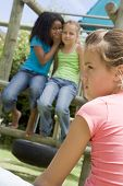 stock photo of peer-pressure  - Two young girl friends at a playground whispering about other girl in foreground - JPG