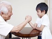 stock photo of wrestling  - asian senior man hand wrestling with grandson - JPG