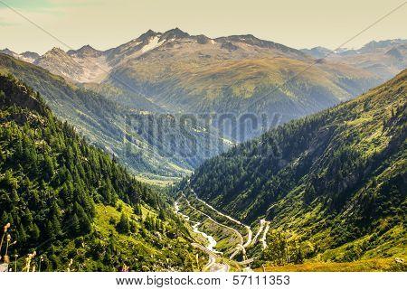 View Through Alps Valley Near Gletch With Furka Pass Mountain Road, Switzerland