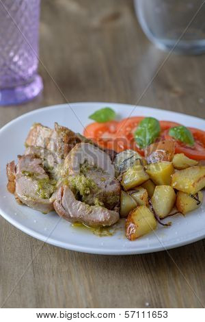 Stuffed Pork Fillet With Tomatoes And Basil On The Side On An Old Wood Table