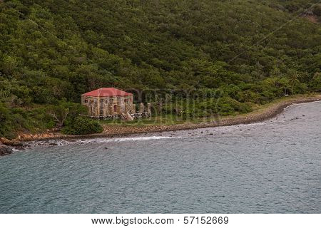 Old Stone Building With Red Roof On Green Coast